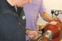 Here we have David Hutcheson (dark top) showing Ian Savage the correct way to use a gouge.