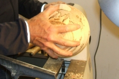 Geoff Potter having completed the outside of his bowl, now turning it around to work the inside.