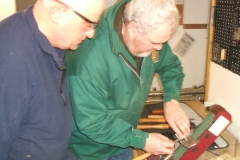 David sharpening a tool on the belt sharpener, being observed by some of the members.