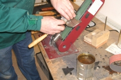 A closer view of how David holds the tool as it's being sharpened, note the position of the tool guide above the belt.