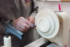 Douglas has shaped the base and can be seen sanding for the finish.