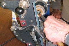 Errol Levings about to sharpen a parting tool with a belted machine.