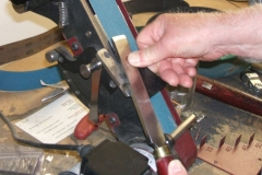 David Hutcheson using a belt tool with the tool guide to sharpen a flat skew.