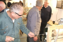 Here Graham Charge is using the long hole boring tool, being observed by some of the members.